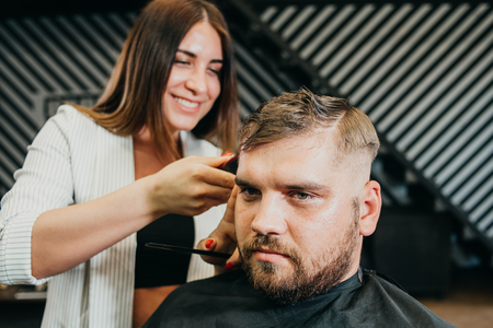woman hairdresser does the hair to a brutal man in the salon Banque d'images - 123972241