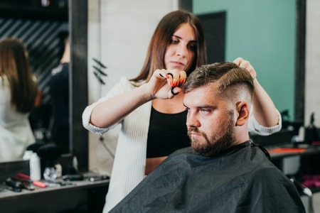 girl hairdresser cuts scissors bearded man in the salon Banque d'images - 123972242