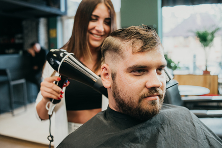 woman hairdresser dries hair to man in salon Banque d'images - 123972332