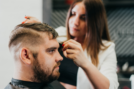 girl hairdresser cuts scissors bearded man in the salon Banque d'images - 123972333