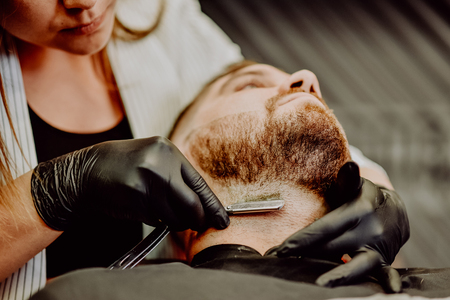 the barber shaves his beard with a man with a razor Banque d'images - 123972338