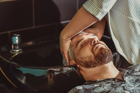 the hairdresser washes his hair with shampoo for a man before cutting Banque d'images - 123972339
