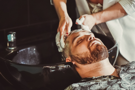 the hairdresser washes his hair with shampoo for a man before cutting Banque d'images - 123972340