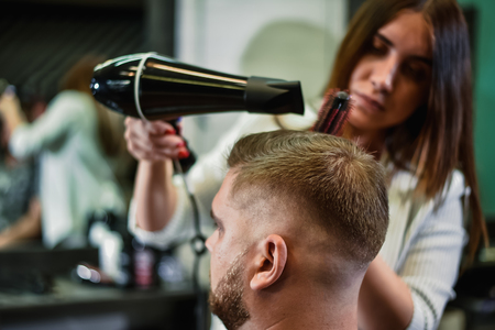woman hairdresser dries hair to man in salon Banque d'images - 123972341