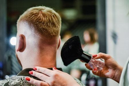 the hairdresser removes hair residues with a brush after shearing Banque d'images - 123972342