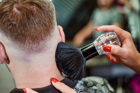 the hairdresser removes hair residues with a brush after shearing Banque d'images - 123972343
