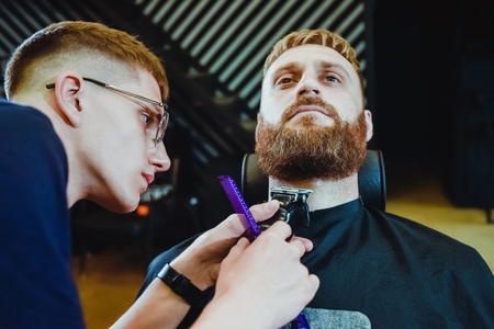 young guy hairdresser cuts beard to man in salon Banque d'images - 123972344