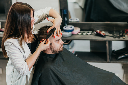 girl hairdresser cuts scissors bearded man in the salon Banque d'images - 123972345