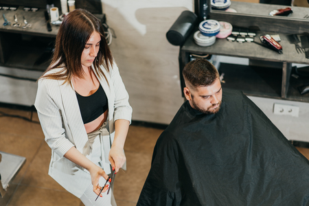 girl hairdresser cuts scissors bearded man in the salon Banque d'images - 123972346