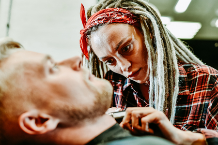 woman hairdresser does the hair to a brutal man in the salon
