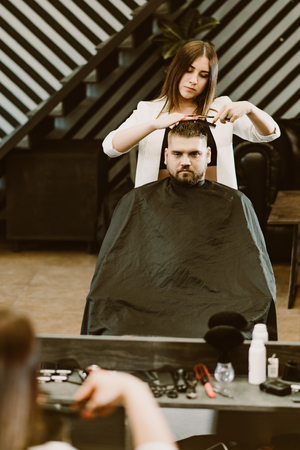 girl hairdresser cuts scissors bearded man in the salon Banque d'images - 123972320
