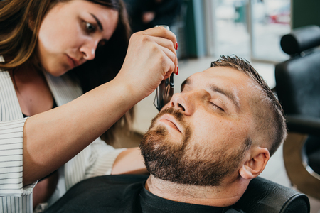woman hairdresser does the hair to a brutal man in the salon Banque d'images - 123972324