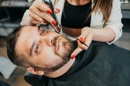 woman hairdresser does the hair to a brutal man in the salon Banque d'images - 123972325