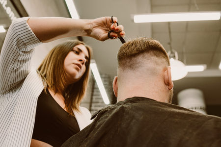 girl hairdresser cuts scissors bearded man in the salon Banque d'images - 123972326