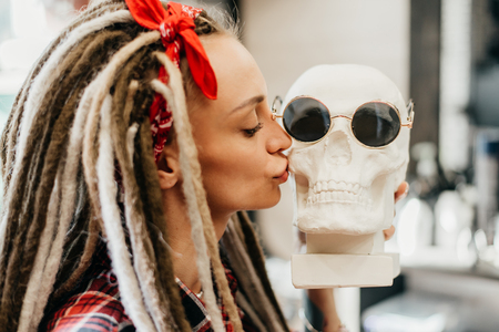 beautiful woman with dreadlocks kisses a skull in sunglasses