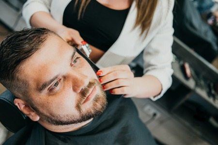 woman hairdresser does the hair to a brutal man in the salon Banque d'images - 123972291