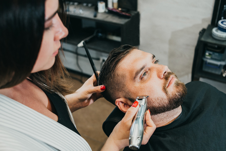 woman hairdresser does the hair to a brutal man in the salon Banque d'images - 123972292