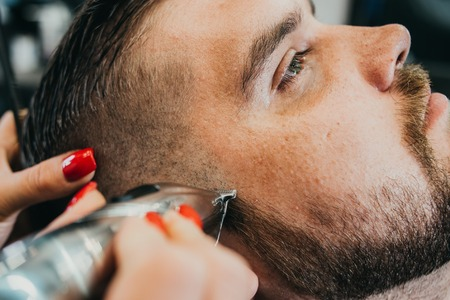 woman hairdresser does the hair to a brutal man in the salon Banque d'images - 123972293