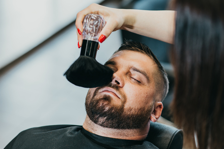 the hairdresser removes hair residues with a brush after shearing Banque d'images - 123972295