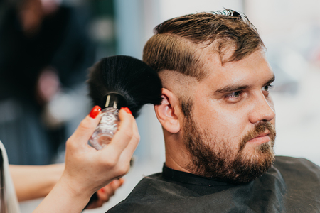 the hairdresser removes hair residues with a brush after shearing Banque d'images - 123972304