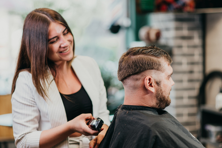 woman hairdresser does the hair to a brutal man in the salon Banque d'images - 123972309