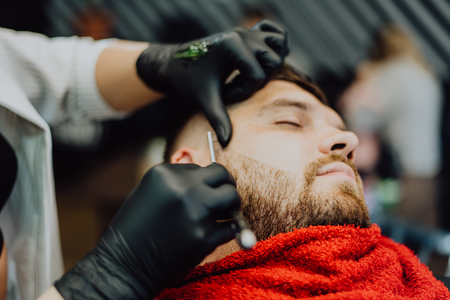 the barber shaves his beard with a man with a razor Banque d'images - 123972278