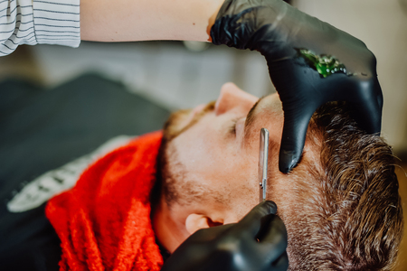 the barber shaves his beard with a man with a razor Banque d'images - 123972279