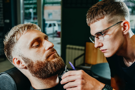 young guy hairdresser cuts beard to man in salon Banque d'images - 123972283