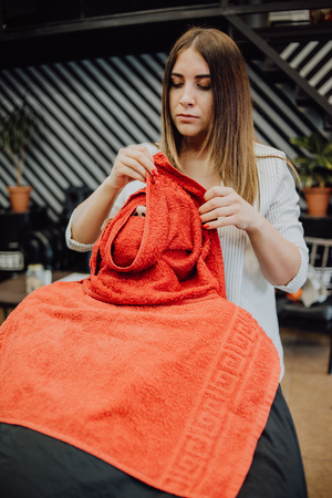 a woman hairdresser wrapped a towel over the client's head before cutting the beard Banque d'images - 123972287