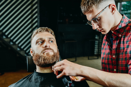 young guy hairdresser cuts beard to man in salon