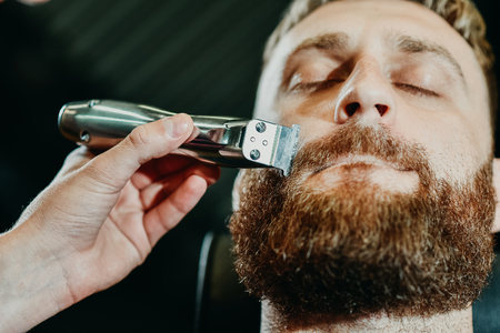 young guy hairdresser cuts beard to man in salon Banque d'images - 123972289