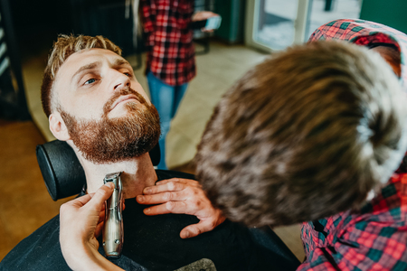 young guy hairdresser cuts beard to man in salon Banque d'images - 123972244