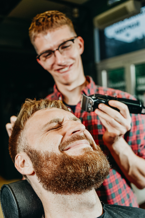 young guy hairdresser cuts beard to man in salon Banque d'images - 123972245
