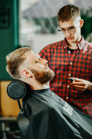 young guy hairdresser cuts beard to man in salon Banque d'images - 123972251
