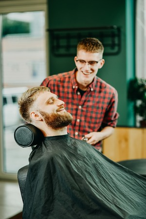 young guy hairdresser cuts beard to man in salon Banque d'images - 123972253