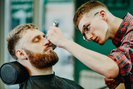 young guy hairdresser cuts beard to man in salon Banque d'images - 123972254