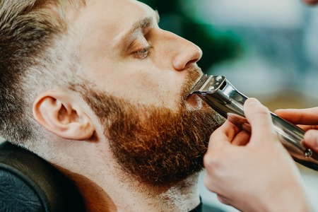 young guy hairdresser cuts beard to man in salon Stock Photo