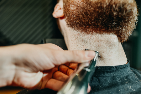 young guy hairdresser cuts beard to man in salon Banque d'images - 123972259