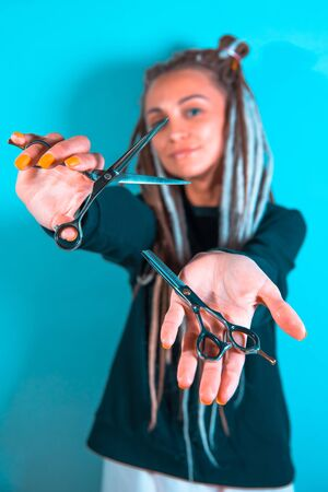 woman hairdresser with dreadlocks holding scissors in hand close-up Banque d'images - 125562170