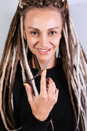 woman hairdresser with dreadlocks holding scissors in hand close-up Banque d'images - 125562172