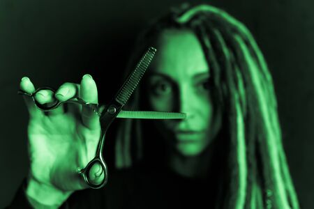 woman hairdresser with dreadlocks holding scissors in hand close-up Banque d'images - 125562176