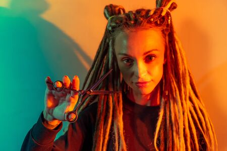 woman hairdresser with dreadlocks holding scissors in hand close-up Banque d'images - 125562180