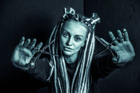 woman hairdresser with dreadlocks holding scissors in hand close-up Banque d'images - 125562182