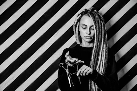 woman hairdresser with dreadlocks holding scissors in hand close-up Banque d'images - 125562191