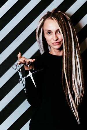 woman hairdresser with dreadlocks holding scissors in hand close-up Banque d'images - 125562192