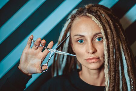 woman hairdresser with dreadlocks holding scissors in hand close-up Banque d'images - 125562193