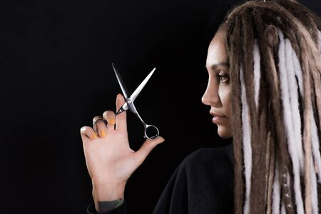 woman hairdresser with dreadlocks holding scissors in hand close-up Banque d'images - 125562254