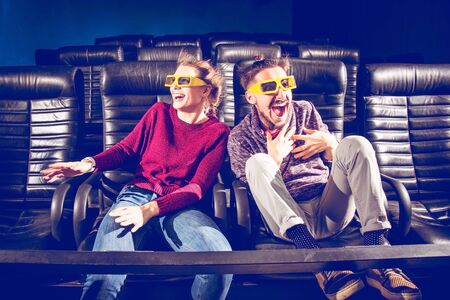 the couple is very worried while watching a movie in the cinema