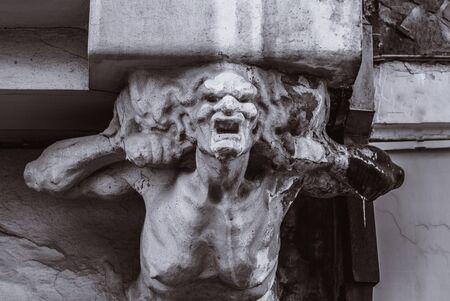 Büste einer schrecklichen Frau an der Fassade eines alten Hauses Standard-Bild