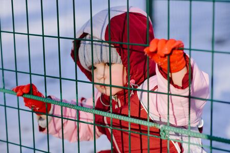 little kid looks through the bars in winter in the park